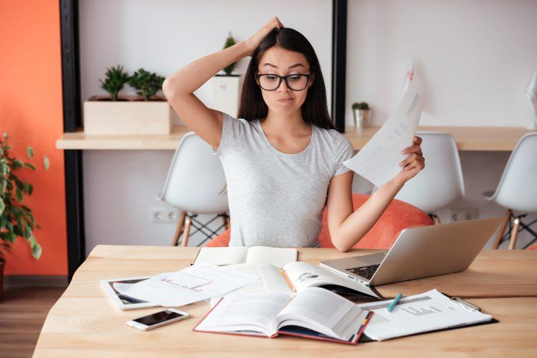 Verwirrte Frau am Schreibtisch